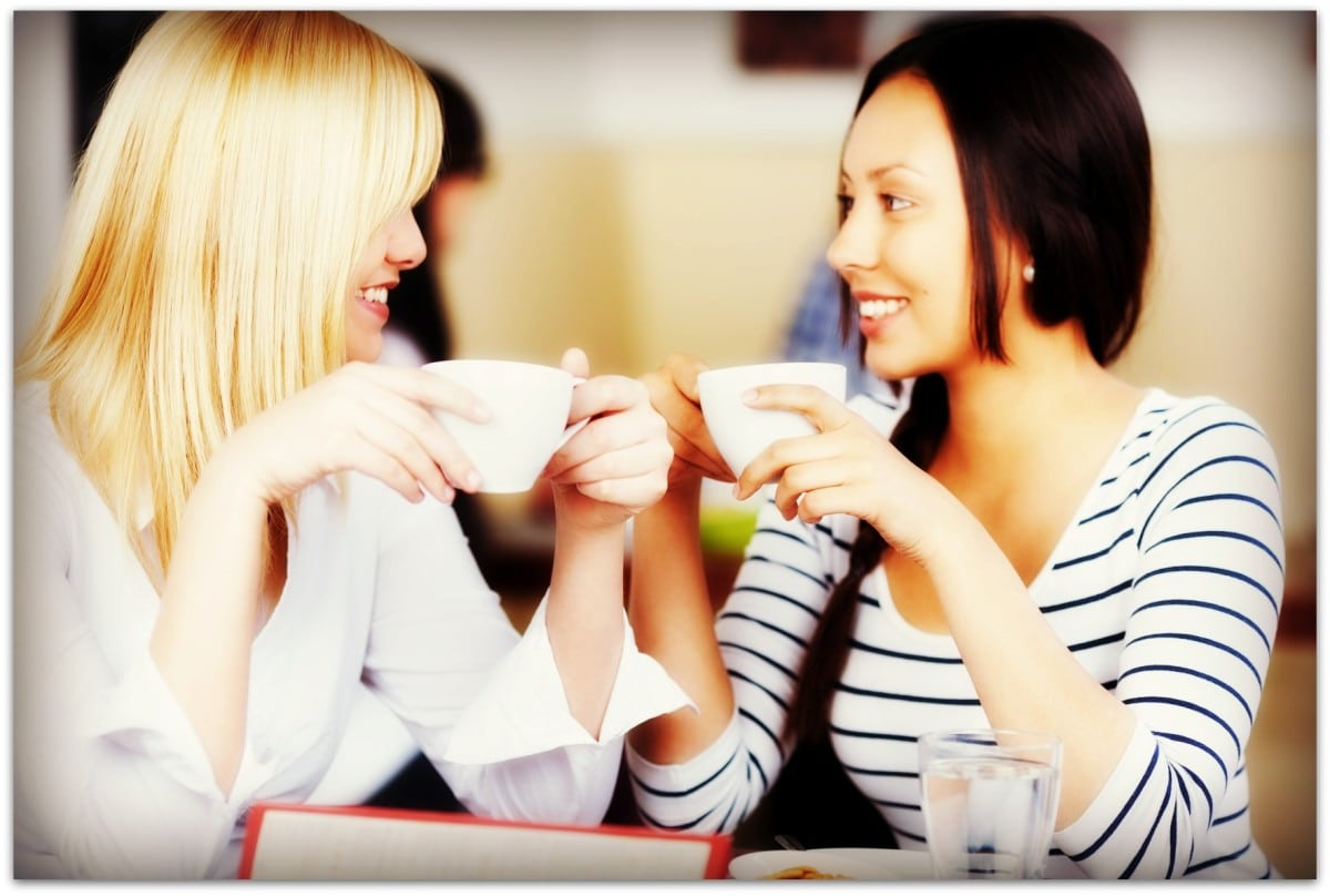 Happy women holding coffee cup while looking at each other in cafe